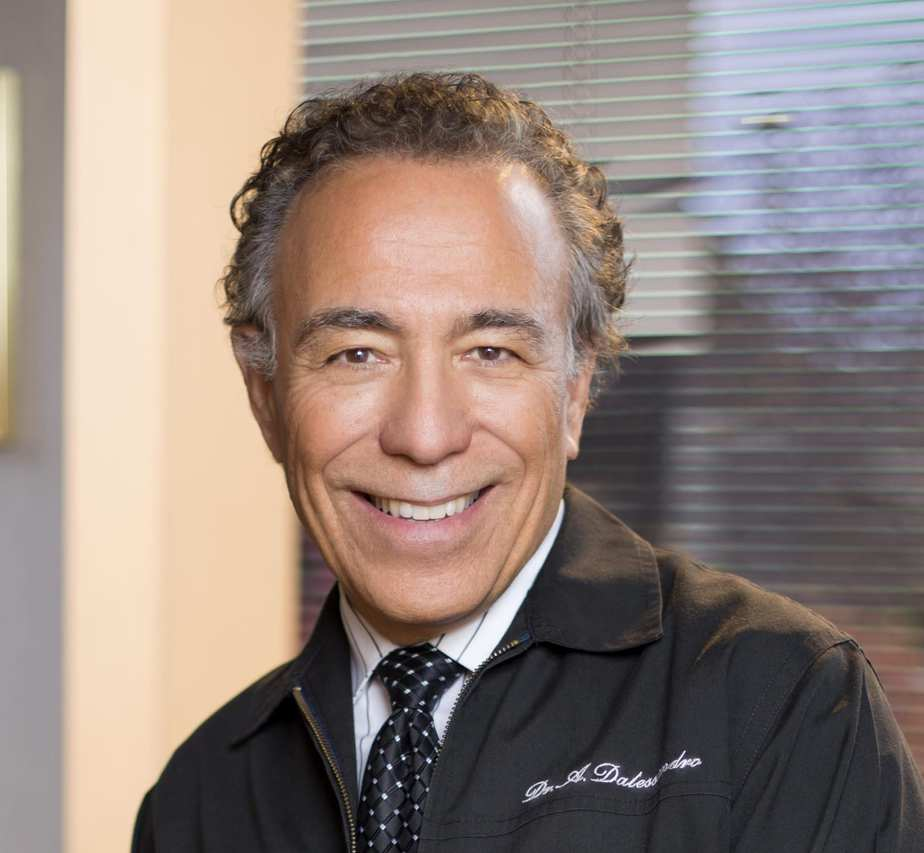 Man smiling in a suit in a dental office